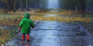 Toddler running in autumn rainy park